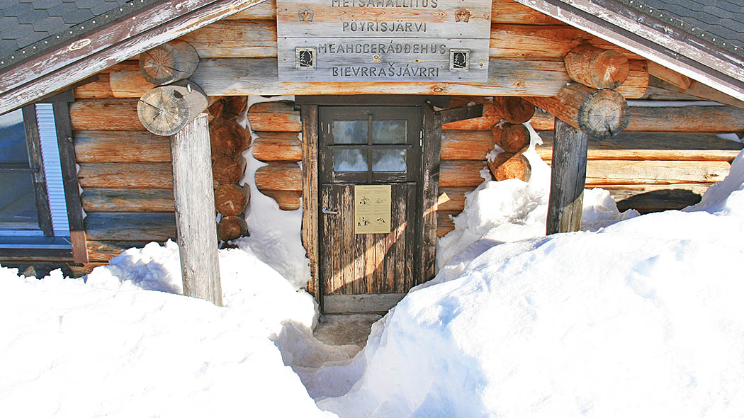 The entrance of Pöyrisjärvi reservable wilderness hut in winter, surrounded by high snowdrifts.