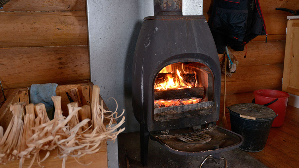 A fire has been lit in the fireplace of the hut.