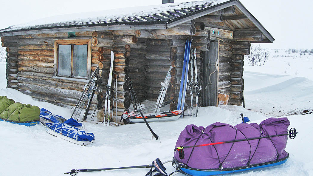 Ropi open wilderness hut in winter. There are several Lapp's sledges and skis in front of the hut.