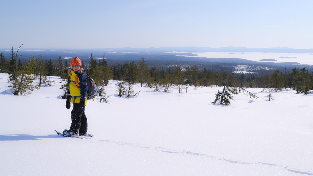A child on snowshoes standing on a fell slope looking at the photographer. A fell- and lake landscape opens up in the background.