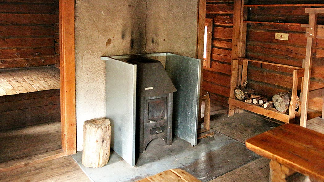 A wood stove and a firewood rack in the hut.