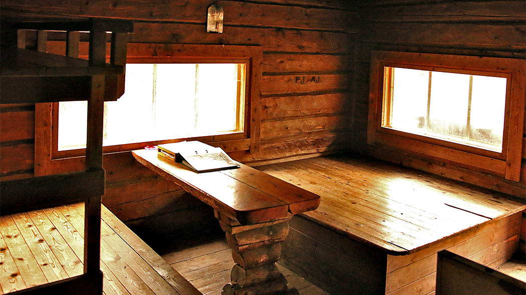 Sleeping platforms and a table in the hut. There's a folder and a guest book on the table.