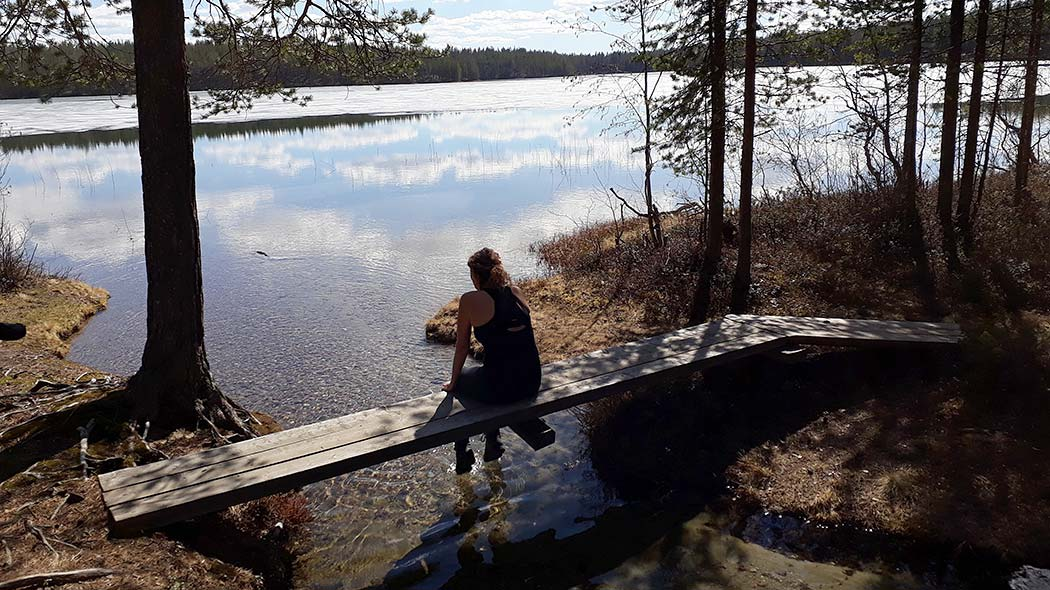 A woman is sitting on a narrow, wooden bridge over a stream, while looking out over a lake where ice is melting.