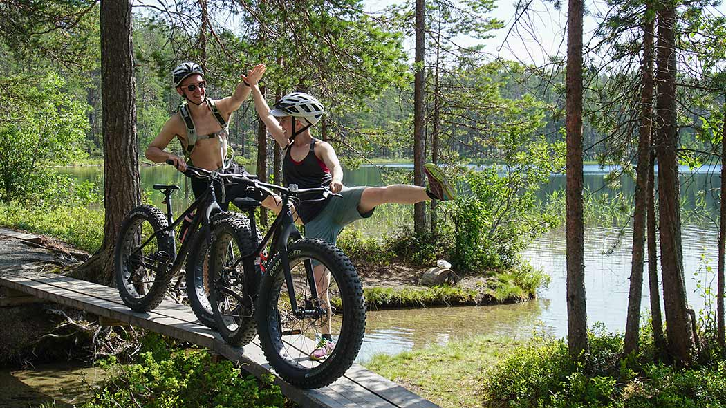 Two cyclists giving each other a high five atop a small, wooden footbridge.