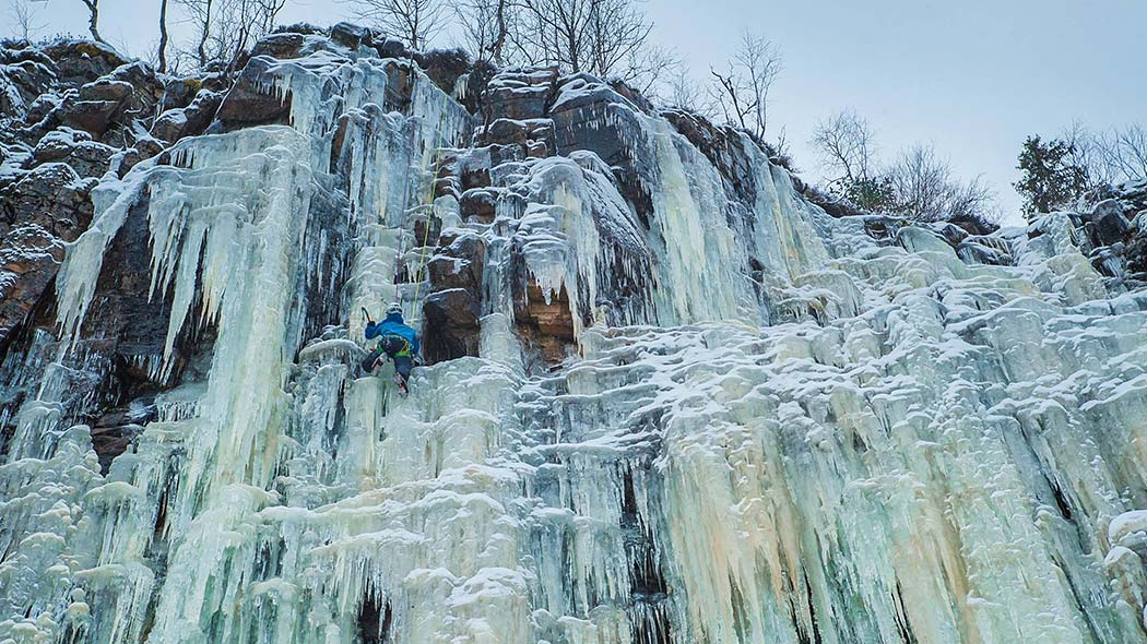 A man climbing on the frozen waterfall on the cliff.