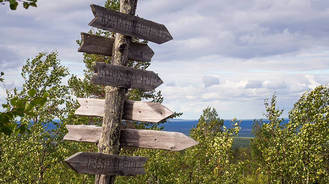 An old signpost with signs to different directions, Texts: Korvatunturi 77, Saariselkä 119, Helsinki 910.