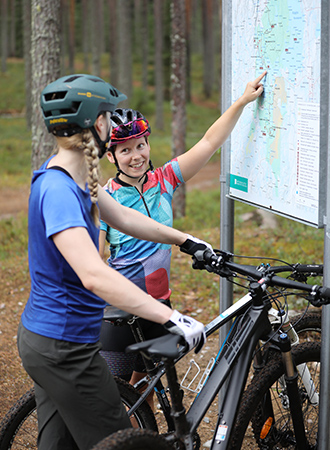 Two mountain bikers have stopped to study a map.