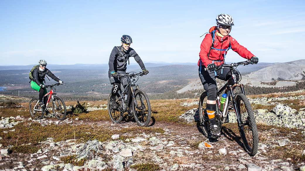 Mountain bikers on a rocky trail with fells and forests in the background.