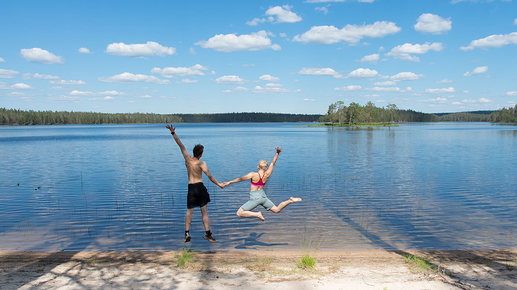 Two hikers are jumping in the air at a summer lake beach.