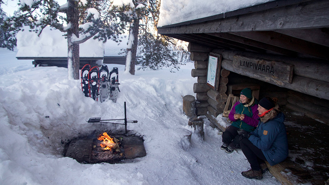 Two persons sitting at a lean-to shelter with a campfire in front of them. Their snowshoes have been set standing on the snow.
