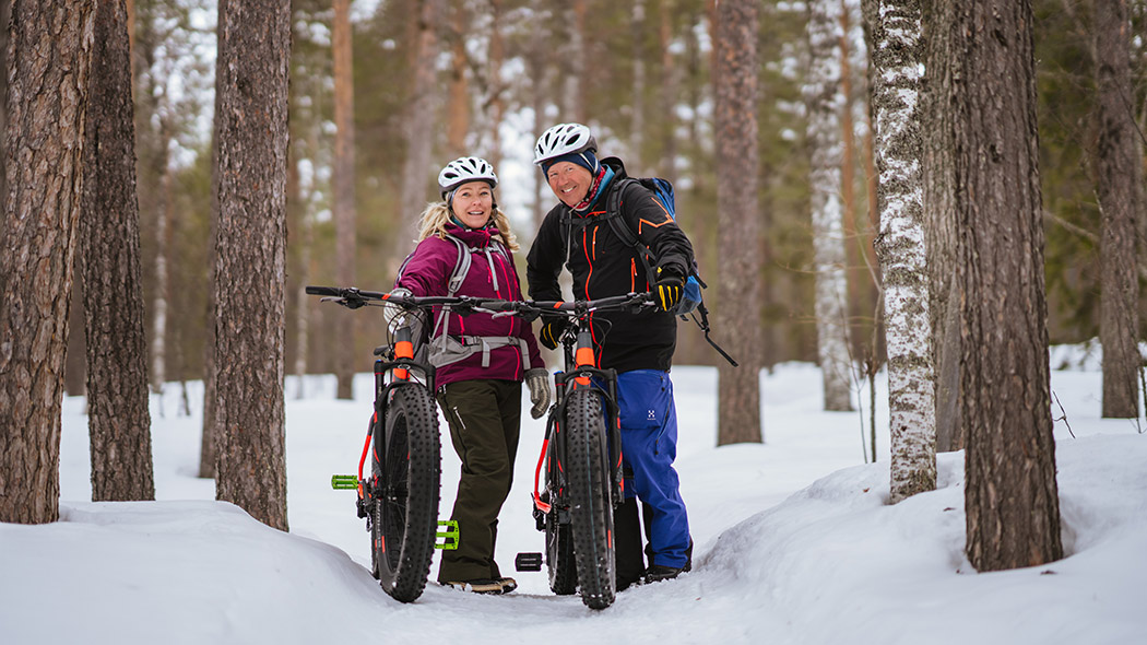 Two persons smiling with their mountain bikes in a snowy landscape.