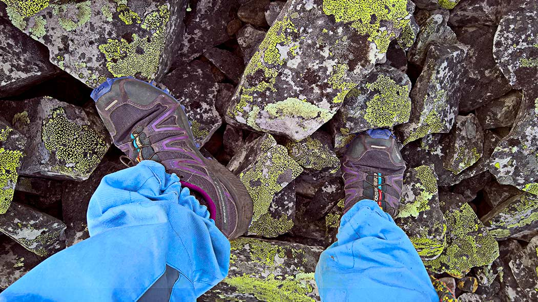 A person with trail shoes standing on rocks, only the feet are visible.