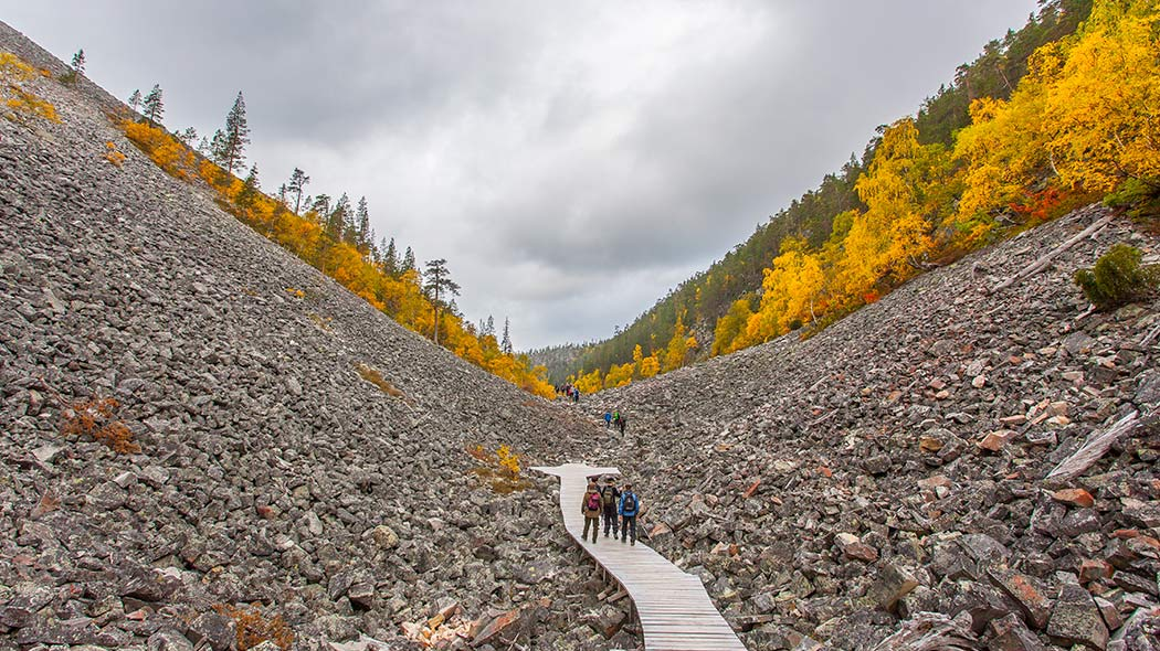 People walking at the bottom of a gulch in autumn nature.
