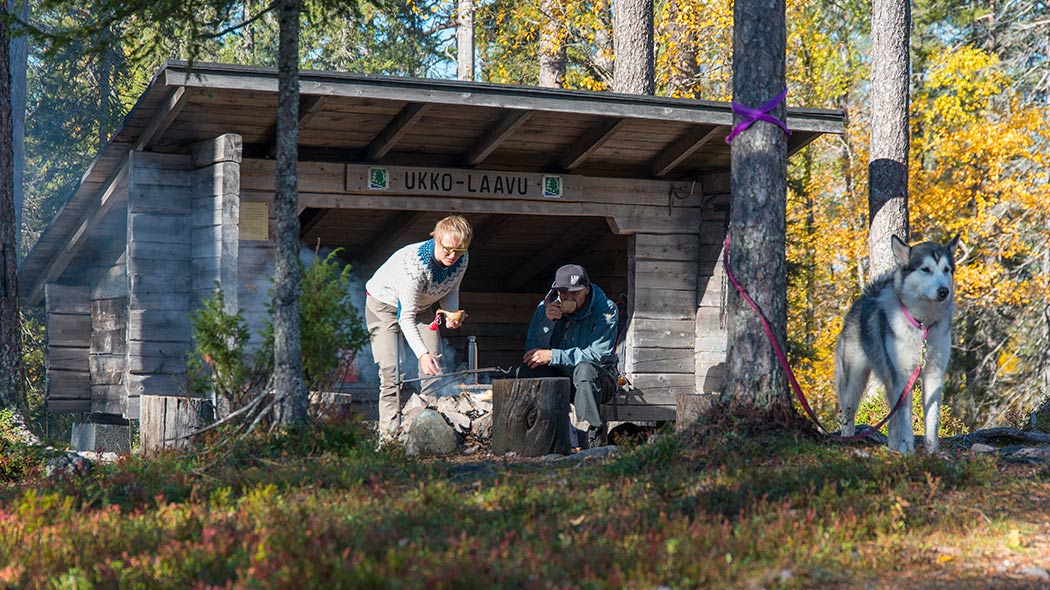 Two persons at a cooking area in front of a lean-to shelter. There's a dog on a leash tied to a tree next to them.