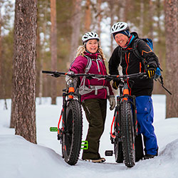 Two cyclists smiling with their mountain bikes in a winter landscape.
