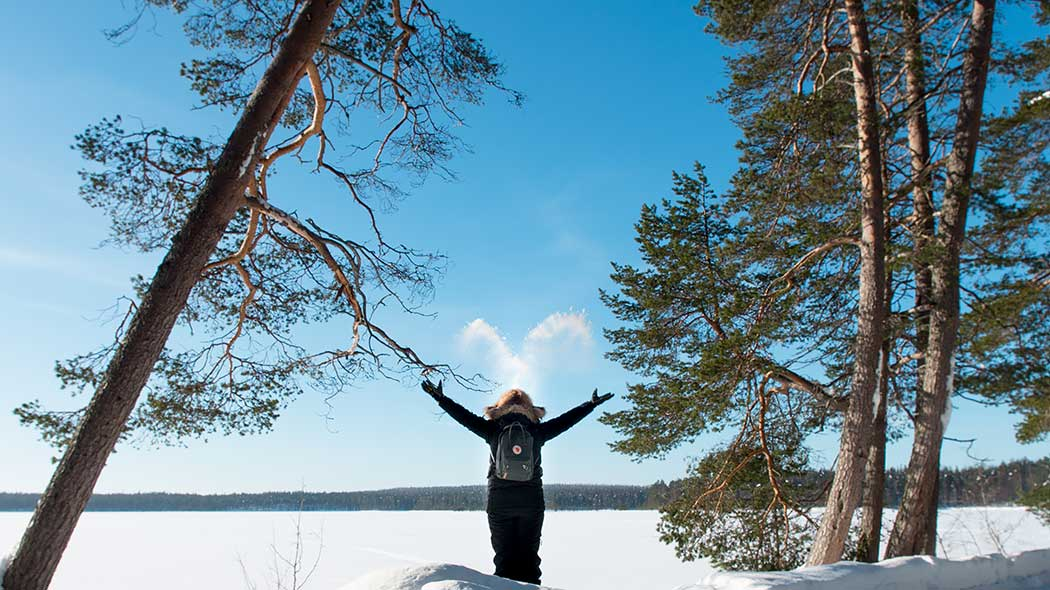 A woman standing on the lake shore in winter, facing the lake. Lake is covered with snow.