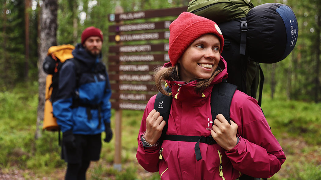 Two hikers carrying backpacks in front of some signs. One of the hikers is in the foreground, the other in the background.