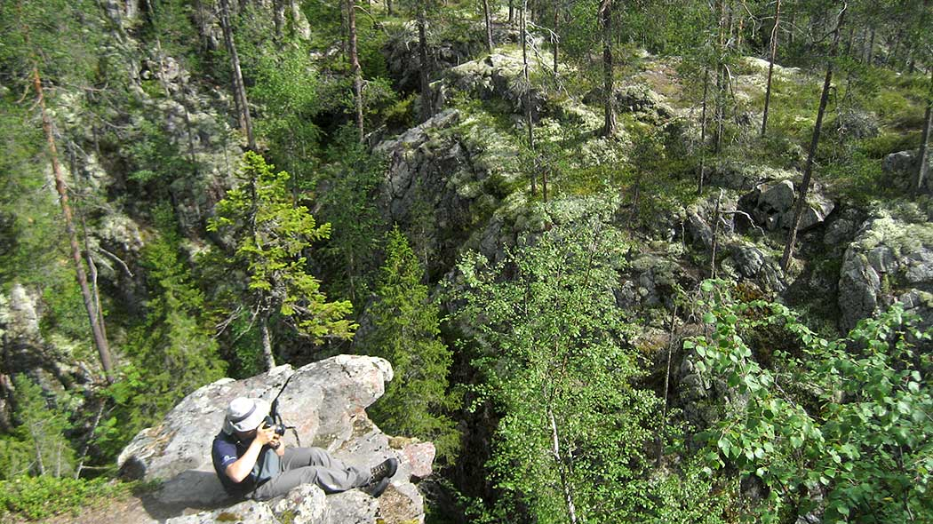 A photographer sits on a cliff atop a gorge, taking pictures of a summer valley. In the background you can see the other edge of the gorge, which is covered in mosses and trees.