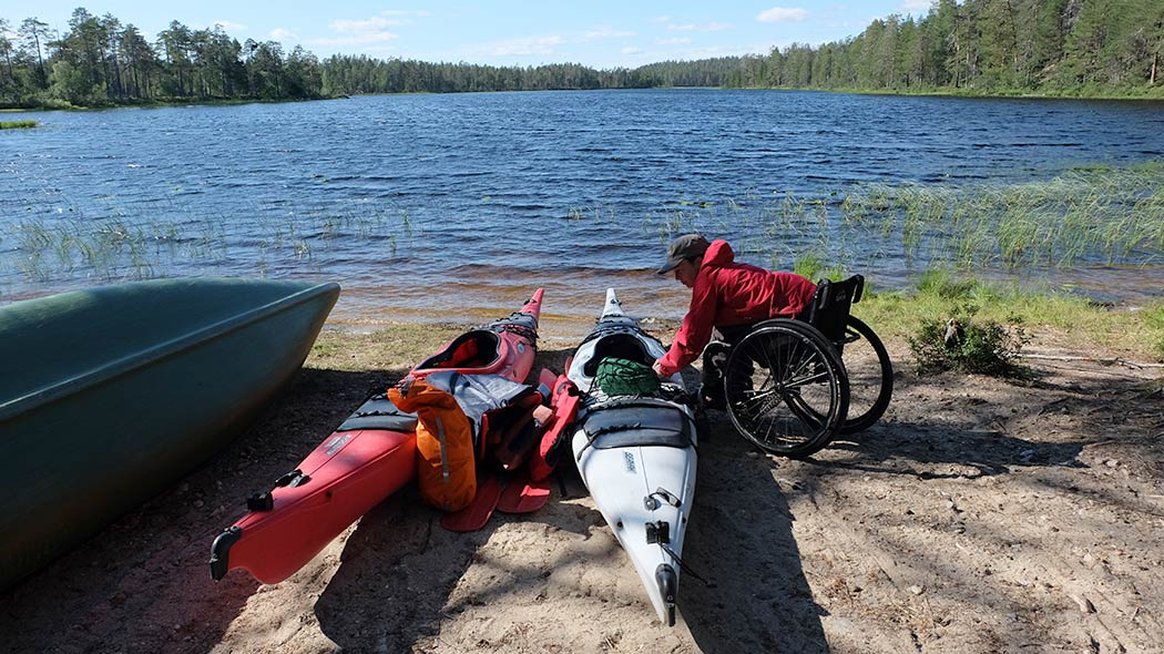 A hiker in a wheelchair packs a kayak by a lake. Another kayak is adjacent to the first.