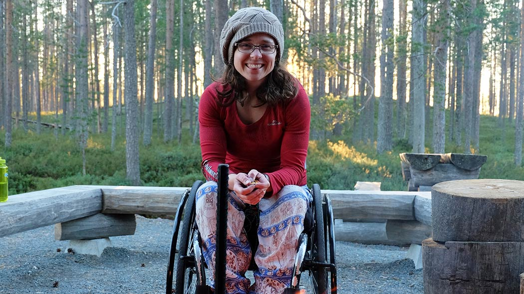 A smiling hiker in a wheelchair sits in front of a campsite with a campfire.