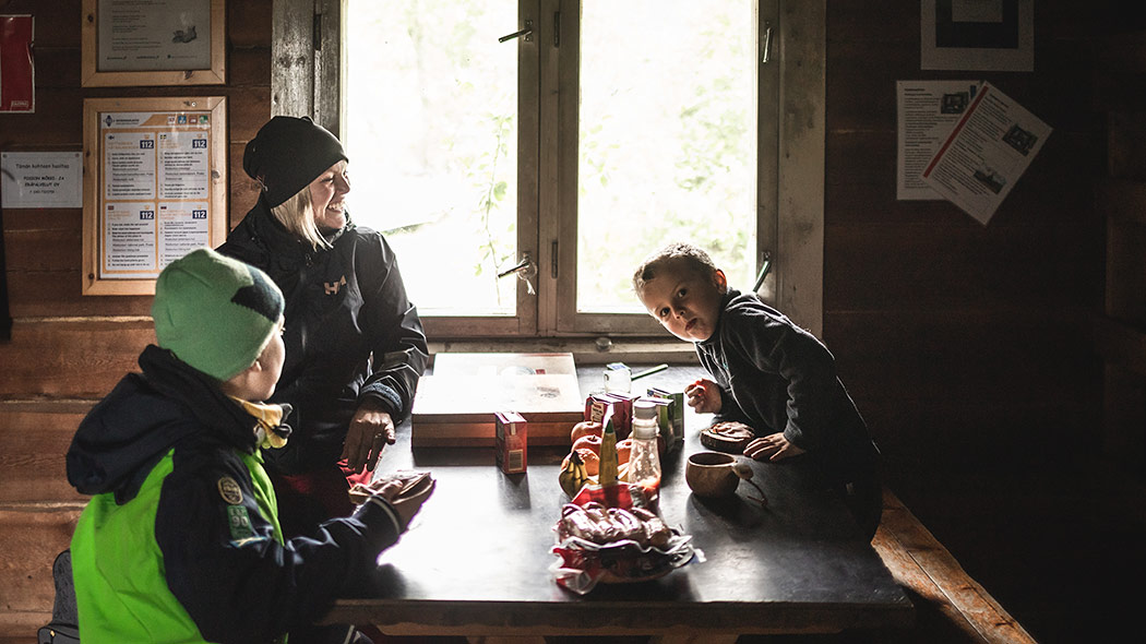 A hiker and two children eating snacks at the table in an open wilderness hut.